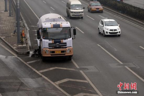 近日,北京环卫集团出动多辆洒水清扫车,对路面及时进行除尘降尘处理。按照《北京市空气重污染应急预案》,空气重污染红色预警期间,全市范围内500多万辆机动车实施单双号行驶措施。与此同时,为保障限行期间市民出行不受影响,北京市交通委根据客流情况采取增发车辆等措施,确保重点道路和轨道交通运营秩序正常,地面公交增加2.1万车次。此外,地铁各线也增加1成车辆备勤,并根据客流情况适时延长运营时间、加开临客。 中新网记者 金硕 摄