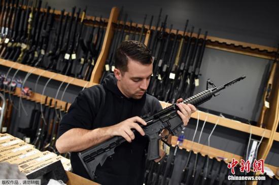 当地时间2015年12月9日,美国新泽西州Randolph,民众在RTSP射击馆买枪,练习射击。加州枪击案后,奥巴马采取更为严厉的枪支管制措施,但部分民众依旧选择了依赖枪支以求防身。图为工作人员在展示出售的枪支。