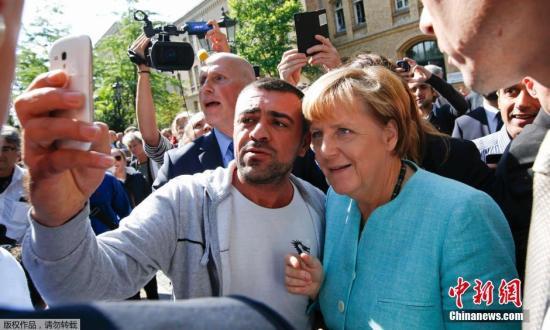 柏林的一處難民營外,一位移民拿起手機與默克爾自拍合影。