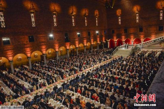资料图:当地时间2015年12月10日,瑞典斯德哥尔摩,诺贝尔晚宴举行,诺奖获得者和王室成员出席了晚宴。在斯德哥尔摩市政厅气势恢宏的蓝厅,1300名嘉宾同时用餐,一批经过严格挑选的宾客应邀出席世界上最具吸引力的社交活动:诺贝尔晚宴。