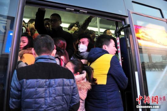 """12月11日清晨,位于河北燕郊的燕灵路口公交站,前往北京的上班一族正焦急的等待着,其中有当地人在京工作的,也有北京人在当地居住的。这座紧靠北京的城市,距离天安门只有30公里,西北距首都机场25公里。约有30万在北京工作的上班族,他们每天披星戴月,奔波于北京与燕郊之间。京津冀交通一体化的推进,一定程度上方便了候鸟们的""""双城生活""""。目前,每天往返两地的公交车已开通12条线路,车辆超过2000个班次,站点和路线也在持续完善。图为赶去北京上班的市民拥上公交车。 翟羽佳 摄"""
