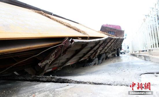"""""""这路面11月25日才铺的,没发现有地下水渗漏致地下空洞的情况。""""在现场的市政施工人员说。 图片来源:视觉中国"""