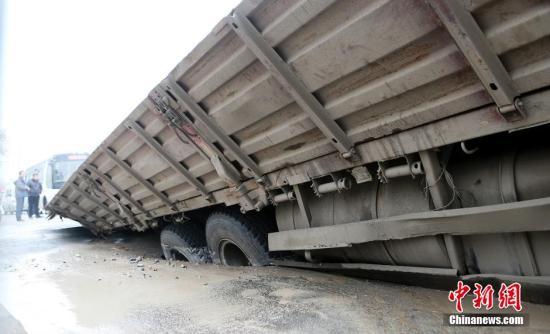 """""""早上6点左右吧,我开车走到十字这儿,突然几声异响,车就往右倾斜,像是陷了下去。""""货车司机说,""""下车一看,道路下陷,货车右侧都陷到路下1米处了。""""华商报记者在现场看到,因右侧下陷到路面以下导致货车整车倾斜。 图片来源:视觉中国"""