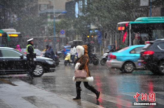 12月16日,受到强冷空气影响,昆明城区降下今冬以来首场雪,对于多年不见雪花的昆明市民来说下雪就像过节一样,随处可见顶风冒雪的民众在路边拍照,玩雪。刘冉阳 摄