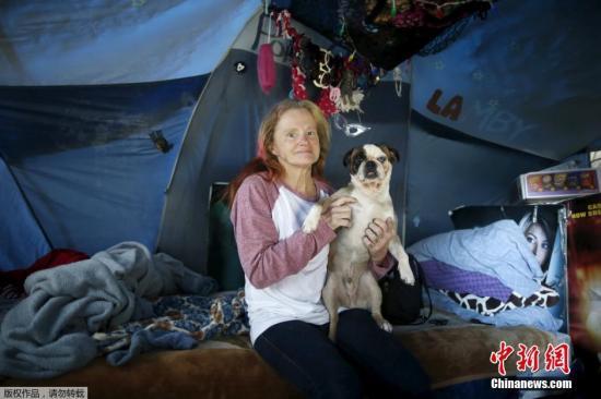 """54岁的福克斯和她的爱犬""""猪排""""。过去的14个月她在高速公路边生活,近来她总感觉这样的生活很危险,十分想过回以前的生活,想念自己的公寓。"""
