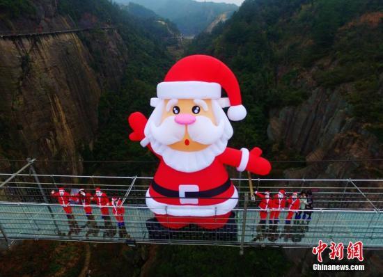 """资料图:一个近10米高的巨型""""圣诞老人""""亮相湖南平江石牛寨玻璃桥,呆萌可爱的形象吸引了众多游客前来合影留念。杨华峰 摄"""