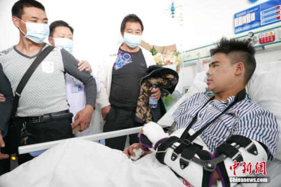 深圳滑坡灾祸幸存者田泽明与父亲病院团圆。中新社记者 陈文 摄
