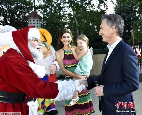 资料图:2015年,阿根廷总?#38472;?#20811;里与到访总统府的圣诞老人握手,妻子和女儿在旁边微笑注目。