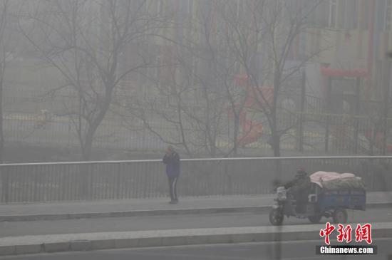 资料图:市民掩住口鼻在雾霾中穿行。
