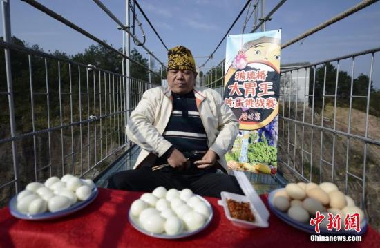 """""""湖南大胃王""""潘一中在近30分钟的挑战时间内,吃下了36个熟鸡蛋和一盘面包虫。 杨华峰 摄"""
