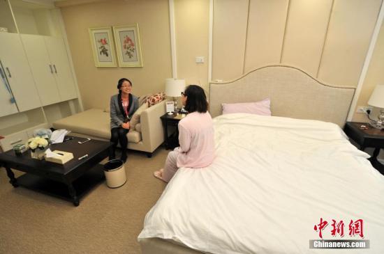 资料图:一家月子中心内客服人员与坐月子的妈妈聊天。吕明 摄