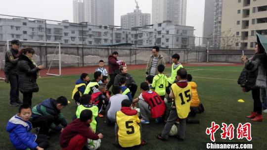 资料图:教练给当地学生讲解足球战术。钟欣 摄