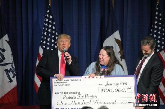 资料图:美国总统竞选人特朗普举行拉票活动。图为特朗普向当地社团捐款。记者 邓敏 摄