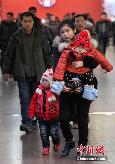 资料图:2月3日,山西太原火车站,一名旅客带着她的两个孩子返乡过年。。中新社记者 韦亮 摄