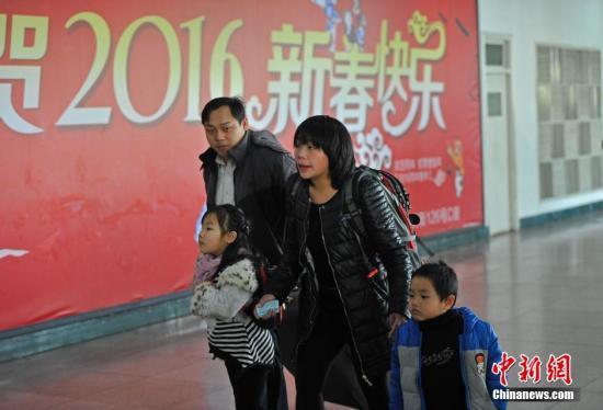资料图:山西太原火车站,一对夫妻领着他们的两个孩子匆忙赶车。中新社记者 韦亮 摄