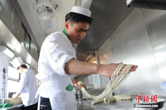 """在2016年春运铁路线上,兰州至上海的Z218次列车餐车为旅行中的旅客提供兰州牛肉面。据担当本次列车行驶任务的兰州铁路局兰州客运段工作人员介绍,列车上的""""兰州牛肉面馆""""是这趟旅游列车的特色,在旅途中常态化地为旅客提供现点、现场制作兰州牛肉面,能让旅客品尝到""""三细、二细、韭叶、大宽""""等特色兰州牛肉面。杨艳敏 摄"""