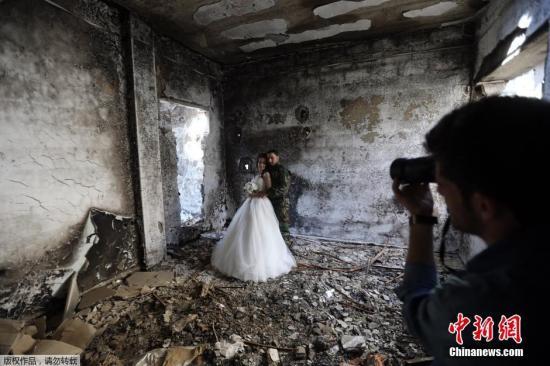 当地时间2月5日,叙利亚霍姆斯一对新婚夫妇Nada Merhi和Hassan Youssef 以饱受战争蹂躏被毁的建筑为背景拍摄婚纱照。
