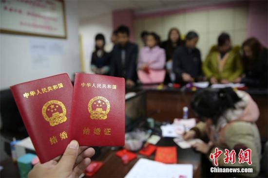 资料图:新人在展示刚领取的结婚证书。 兰自涛 摄