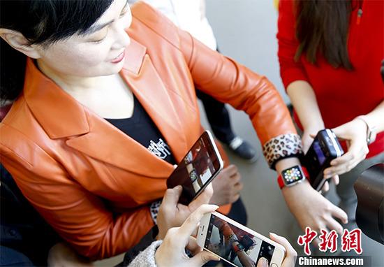 """2月18日,中国银联宣布,即日起银联云闪付正式开通支持Apple Pay服务,中国境内的持卡人可以轻松将他们的银联卡添加到 iPhone、Apple Watch 以及iPad上,在""""银联云闪付""""线下商户及线上APP更加便捷安全地支付。目前,中国国内已有近20家主要商业银行支持此项服务。图为在北京王府井一家商场中国银联助理总裁胡莹体验Apple Pay服务。 中新社记者 杜洋 摄"""