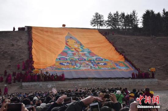 """2月20日,农历正月十三,有着""""世界藏学府""""之称的甘肃拉卜楞寺举行了一年一度的正月晒佛节。当天,伴着蓝天白云和温和的阳光,覆盖在巨幅佛像唐卡上的黄色丝绸缓缓拉开,巨大佛像出现在拉卜楞寺前的晒佛台上,引得数万藏族民众及游客纷纷赶来瞻仰神圣佛容。 拉卜楞寺位于甘肃省甘南藏族自治州夏河县,是藏传佛教格鲁派六大宗主寺院之一,始建于1709年,迄今已有300多年历史。每年自农历正月初三开始,拉卜楞寺都要举行一年一度的正月法会,晒佛法会是正月法会的重要内容之一。何龙 摄"""