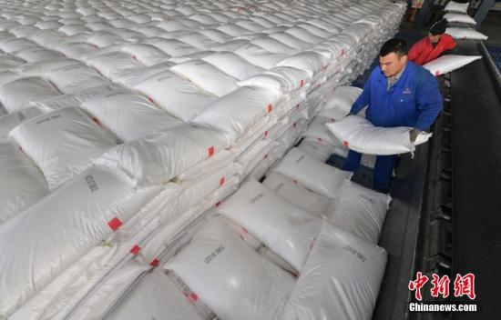 """3月2日,新疆塔里木油田公司石化分公司(库尔勒市)已生产储备9万吨""""放心肥"""",以满足今春南疆地区春耕用肥需求。猴年春节过后,新疆南疆各地州春耕工作陆续开始。图为工人把已生产好的化肥准备往外运。 确・胡热 摄"""