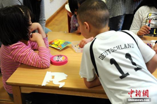 资料图:德国首都柏林一处难民收容所内,几名儿童在志愿者带领下做益智游戏。 彭大伟 摄