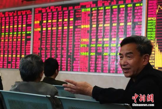 资料图:某证券交易大厅内股民正讨论股市走势。中新社记者 刘忠俊 摄
