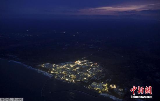"""资料图:当地时间2018-12-12,,""""3-11""""大地震5周年纪念日的前一天,福岛第一核电站在黄昏中停运亮灯的场景。福岛第一核电站位于大熊町,曾在""""3-11""""大地震引发的海啸中受损。"""