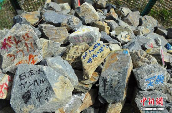 石卷灾区高规格修复被海啸毁损的河道堤坝的工程正在进行中,图为设置在岸边供民众题字寄情的岸基用石,已经写满了各种励志字样。 王健 摄