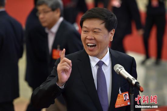 """3月13日,十二届全国人大四次会议在北京人民大会堂举行第三次全体会议。国家税务总局局长王军在两会""""部长通道""""接受记者采访。 中新社记者 金硕 摄"""