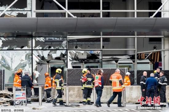 资料图:比利时布鲁塞尔遭到爆炸袭击的机场,爆炸后工作人员清理玻璃碎片。
