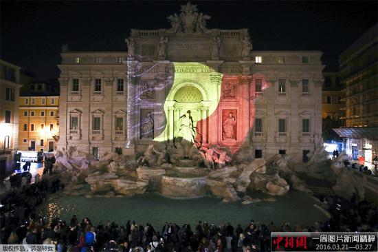 资料图:意大利特莱维喷泉点亮比利时国旗色灯光,悼念布鲁塞尔恐袭遇难者。