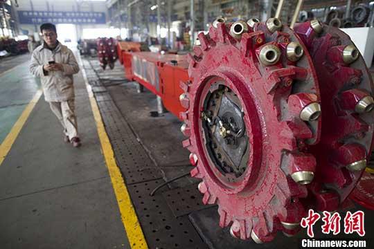 资料图:山西太重工人从采煤机前经过。/p中新社记者 张云 摄