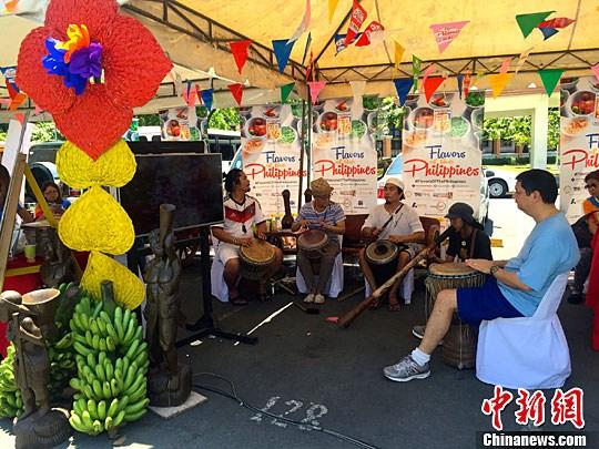 资料图:在菲律宾首都大马尼拉地区马卡蒂市一个旅菲外国人经常光顾的周末集市上,一群艺人在表演,为菲国传统美食推广活动助兴。 中新社记者 张明 摄