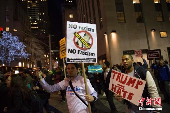 当地时间4月14日晚,民众在纽约洛克菲勒广场附近进行反特朗普游行。 <a target='_blank' href='http://www.chinanews.com/'>中新社</a>记者 廖攀 摄