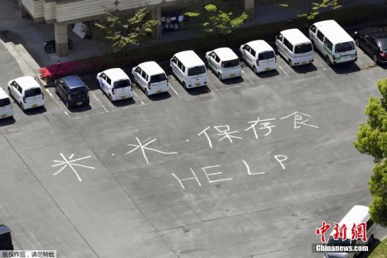 """日本九州于当地时间4月16日凌晨发生里氏7.3级地震。据日媒报道,以熊本、大分两县为中心接连发生地震的灾区本月18日迎来了主震后的首个工作日。据统计,目前死者已增至42人、9人下落不明。图为当地时间4月17日,日本熊本县御船镇福利中心地上写着""""大米、水、腌制食品和HELP""""的求助信息。"""