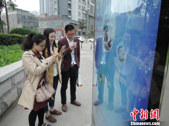 """郑州多功能路牌提供免费WIFI 路人扎堆""""蹭网""""。 韩章云 摄"""