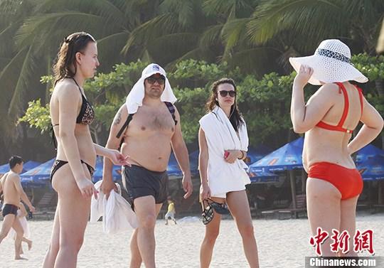 外国游客在三亚大东海海滩上休闲度假。 中新社记者 尹海明 摄