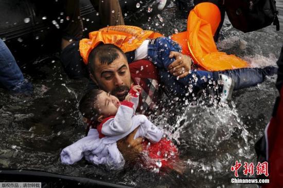 一名叙利亚难民搂着自己的孩子想要登上救生艇。