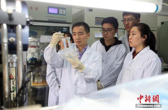 """4月21日,哈尔滨工业大学正式对外发布,该校生命学院教授黄志伟及其团队首次揭示了CRISPR-Cpf1识别crRNA的复合物结构。该项研究成果让人们可以更加高效地对目的基因进行""""关闭""""、""""恢复""""和""""切换""""等精准""""手术"""",使战胜癌症和艾滋病等疾病成为可能。图为4月18日,黄志伟教授与团队成员在校实验室内工作。中新社记者 于琨 摄"""
