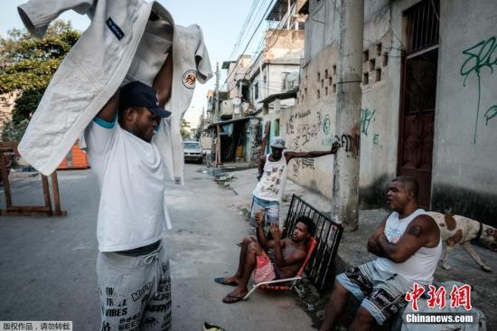 巴西的贫民窟里,Misenga拿着崭新的柔道服展示给邻居们看。
