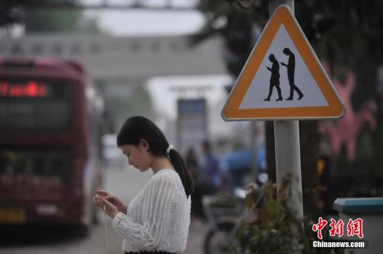 资料图:重庆涪陵一处警示牌,提醒市民在过斑马线的时候不能玩手机,注意交通安全。 陈超 摄