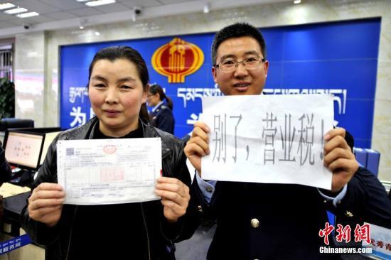 """资料图:2016年5月1日零点,拉萨市国税局西城分局顺利开出西藏首张""""营改增""""不动产经营租赁业增值税发票,西藏全面推开""""营改增""""试点工作准时与全国同步开启。该工作的推行,意味着营业税退出历史的舞台,增值税制度将更加规范。""""营改增""""将会让企业的赋税得到不同程度的下降。 李林 摄"""