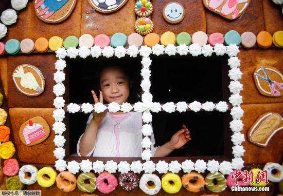 """当地时间5月3日,一名小女孩在""""糖果屋""""玩耍。这座3米高的""""糖果屋""""由3000块蛋糕、饼干和糖果等甜品制成,是2016东京自由之丘甜点节中的一处景观。"""