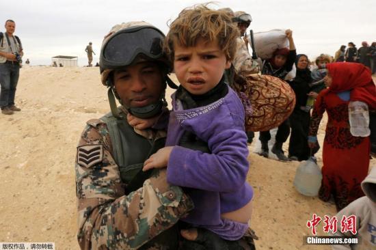 资料图:约旦士兵帮助进入约旦境内的妇女和儿童。