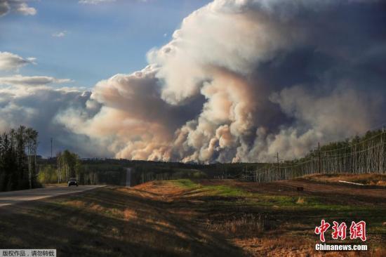 资料图:加拿大阿尔伯塔省麦克默里堡,当地山火持续蔓延,浓烟滚滚。