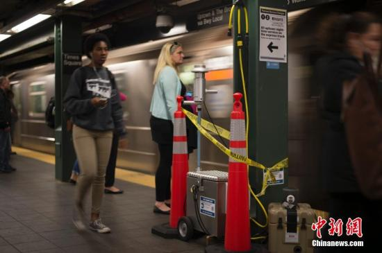 5月10日,纽约地铁时代广场站,乘客走过正在运行的空气采样机,空气采样机检测的是从固定站点释放的无色无嗅惰性气体追踪剂。美国联邦政府9日起在纽约的地铁系统展开防毒气测试,通过释放无害气体研究如何应对有毒物质泄漏事故或化学武器袭击。 中新社记者 廖攀 摄