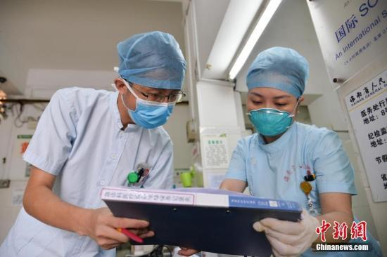 """5月12日,是国际护士节,这一节日设立的基本宗旨是倡导、继承和弘扬南丁格尔不畏艰险、甘于奉献、救死扶伤、勇于献身的人道主义精神。这一天,男护士黄思源和众多护士一样忙碌在医院内,协助医生救死扶伤。今年28岁的黄思源在海南省人民医院秀英院区急诊科已经工作了6年,是全院近1900名护士中为数不多的""""男丁""""之一。他从学校毕业后就自告奋勇地应聘到急诊科,逐渐适应了高强度的工作,如今已成长为一名成熟的护士。上月,他刚被海南省卫计委、海南省护理学会评为""""优秀护士""""。图为黄思源与同事核对需要维护的设备清单。 洪坚鹏 摄"""