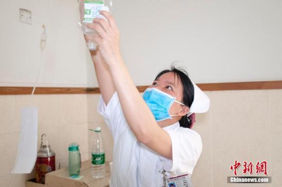 身怀二孩的护士韦金莲为患者更换吊瓶(资料图)。黄威铭 摄