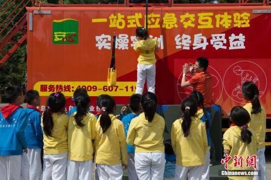5月12日,来自北京市第十八中学附属实验小学的学生在观看应急安全教育儿童剧《奇妙梦旅行》前,在中国儿童剧院前广场体验了由青岛红十字天使救援队等相关单位组织的,包括心肺复苏、灭火器使用、模拟地震等多项应急安全体验活动。图为小学生在进行高层缓降体验。中新社记者 崔楠 摄